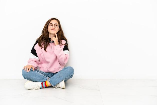 Молодая кавказская женщина сидит на полу, изолированном на белом фоне, думая об идее, глядя вверх