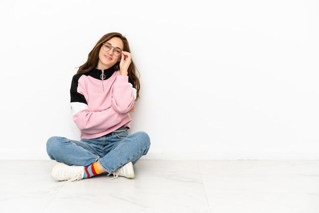 眼鏡と幸せな白い背景で隔離の床に座っている若い白人女性