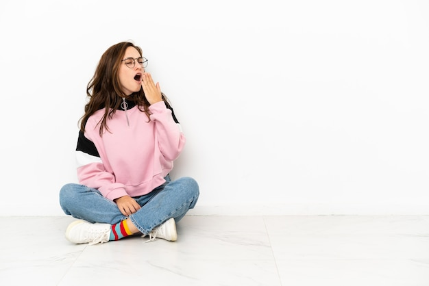 Молодая кавказская женщина сидит на полу, изолированном на белом фоне, зевая и прикрывая широко открытый рот рукой