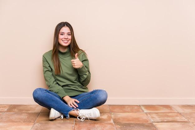 Молодая кавказская женщина сидя на поле изолировала усмехаться и поднимать большой палец руки вверх