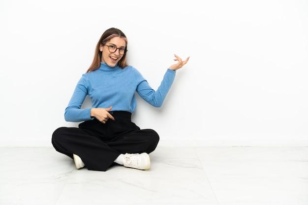 ギターのジェスチャーを作る床に座っている若い白人女性