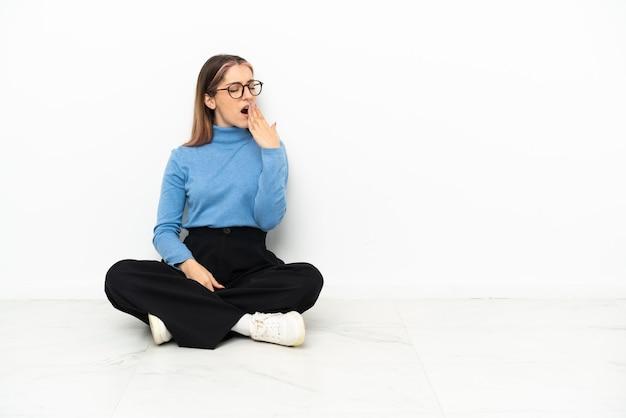 Молодая кавказская женщина сидит на полу, зевая и прикрывая широко открытый рот рукой