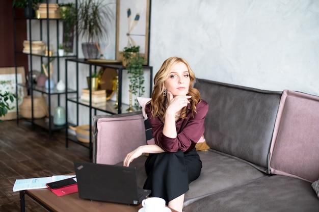 ソファに座って、現代のオフィスで働いている若い白人女性。テーブルの上には、ラップトップ、ノートブック、コーヒーがあります。ビジネスコンセプト