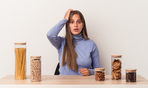 Young caucasian woman sitting at a table with food pot isolated on white background being shocked, she has remembered important meeting.