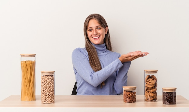 Young caucasian woman sitting at a table with food pot isolated on white background holding a copy space on a palm.