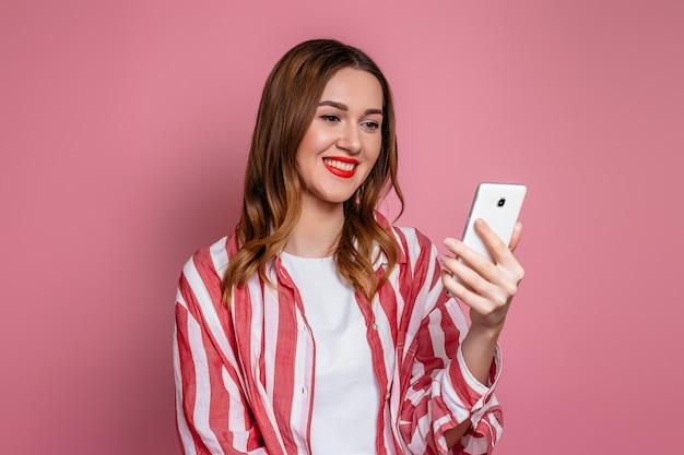 ピンクのスタジオの背景に分離された携帯電話の画面を笑顔で見て若い白人女性。オンラインデートの概念