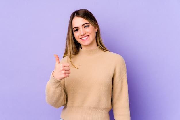 若い白人女性の笑顔と親指を上げる