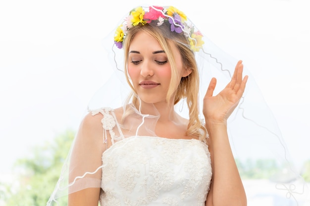 Young caucasian woman smiling and trying on wedding dress in a shop.