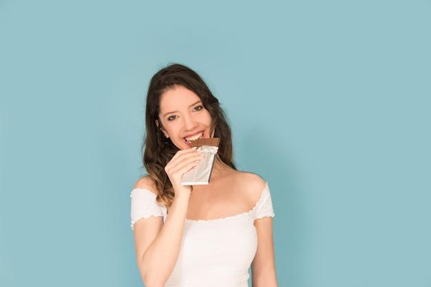 Юнг кавказская женщина улыбается с плиткой шоколада