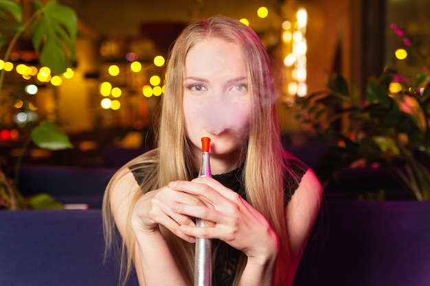 Young caucasian woman smokes a hookah or shisha in the night club or bar smoke