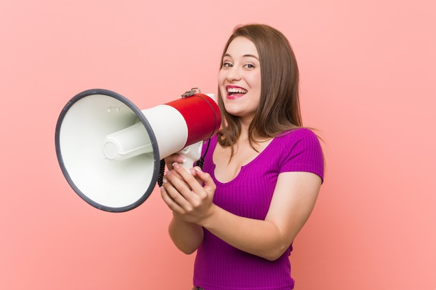 Young caucasian woman speaking through a megaphone
