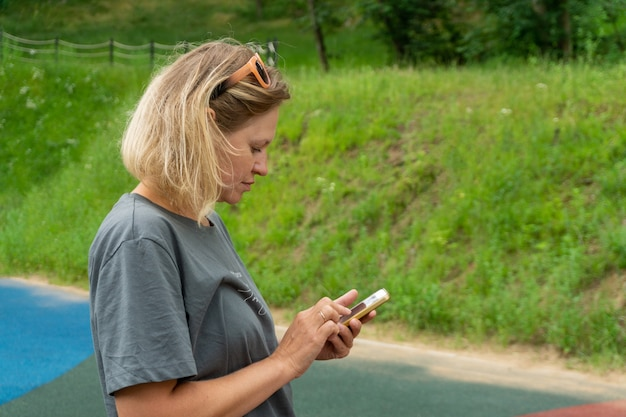 A young caucasian woman in sportswear stands on the street with a phone in her hands.