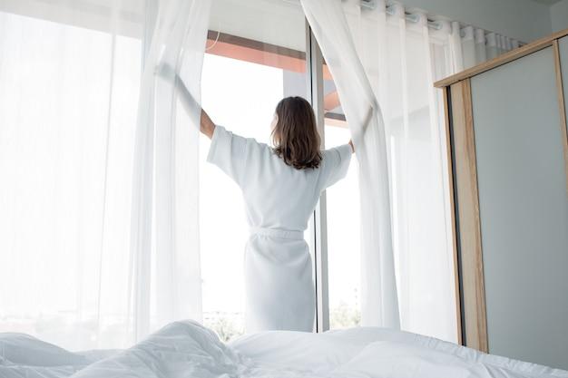 Молодая кавказская женщина стоит за открытыми белыми занавесками у окна на следующее утро после пробуждения в спальне своего дома. женщина просыпается со свежей и распахивает шторы на окнах.