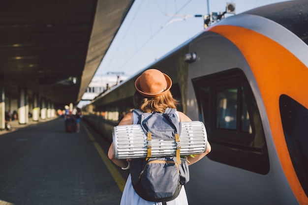 Young caucasian woman standing at train station platform near train backs train