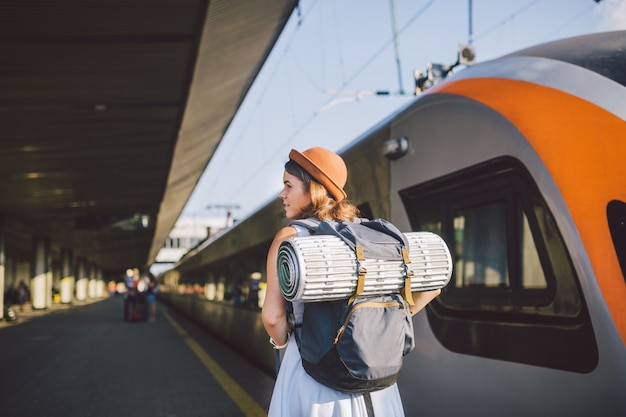 Young caucasian woman standing at train station platform near train