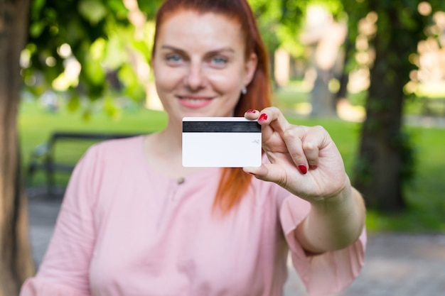Young caucasian woman stay in park and show white credit card with black magnet line.