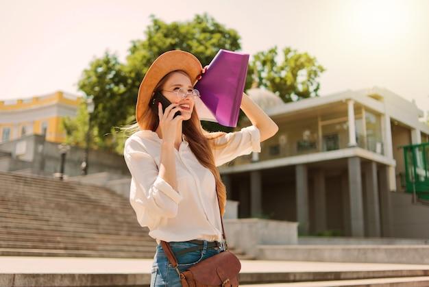 階段を下りて電話で話しているフォルダ内のエッセイとカジュアルな服装の若い白人女性学生