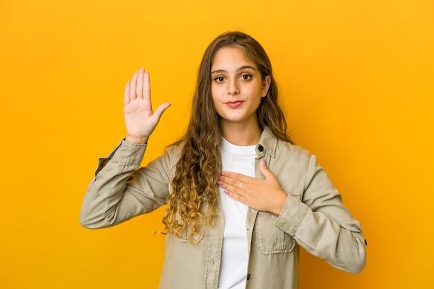 誓いを立て、胸に手を置く若い白人女性。