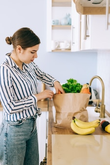 Young caucasian woman taking vegetables from a paper shopping bag in kitchen.