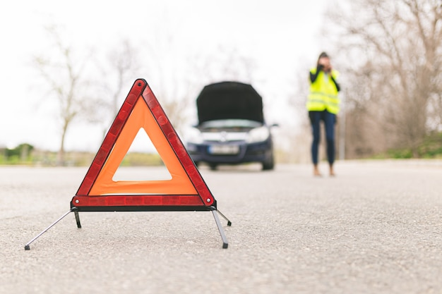 Young caucasian woman, talking on her cell phone while her car is broken down on the road with reflective warning triangles. selective focus. automobile and roadside assistance concept.