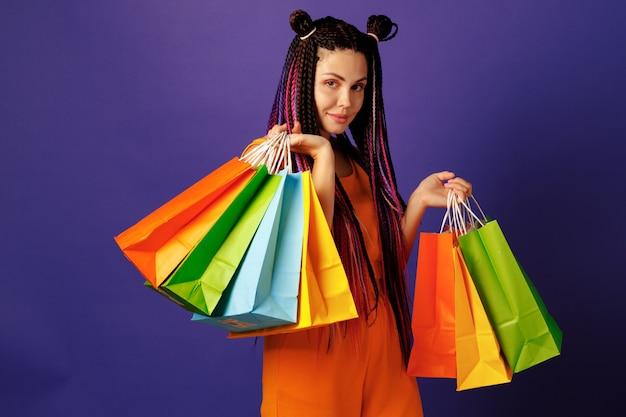 보라색 배경에 화려한 쇼핑 가방 더미를 들고 젊은 백인 여자 십 대