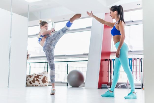 Молодая кавказская тренировка женщины с личным тренером в спортзале практикуя высокие пинки стороны.