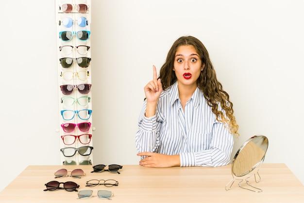 いくつかの素晴らしいアイデア、創造性の概念を持って孤立した眼鏡を試してみて若い白人女性。