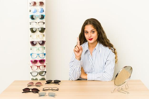 Молодая кавказская женщина пытается очки изолированы, показывая номер один пальцем.