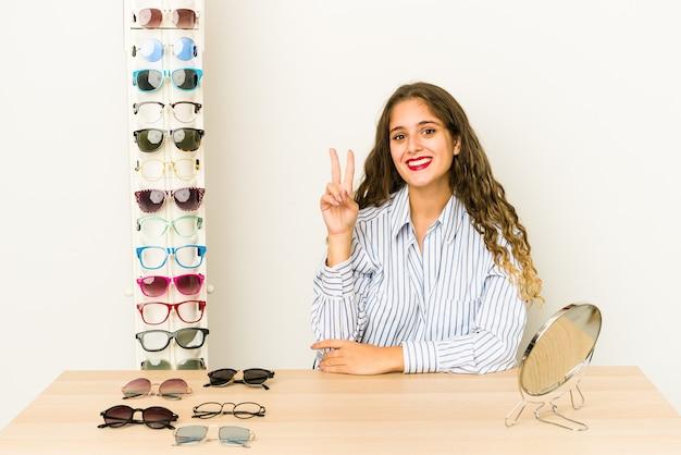 指で2番目を示す孤立した眼鏡を試してみて若い白人女性。