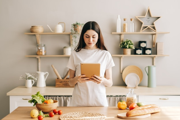 若い白人女性は、サラダを読むレシピを準備するキッチンでタブレットコンピューターを使用します