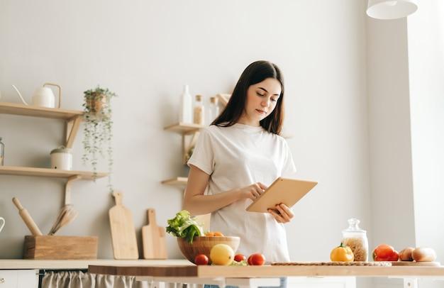若い白人女性は、サラダを読むレシピを準備するモダンなキッチンでタブレットコンピューターを使用します