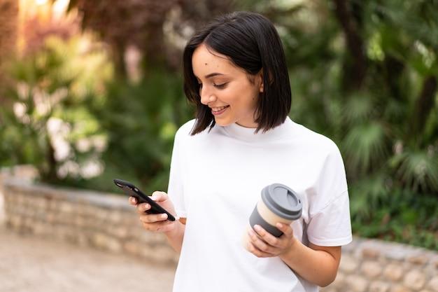Молодая кавказская женщина разговаривает по телефону на открытом воздухе