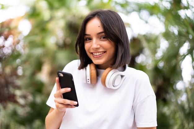 屋外で電話を使用して若い白人女性