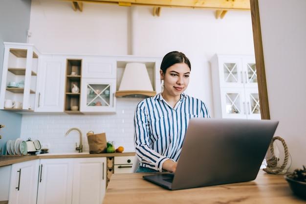 Молодая женщина кавказской с помощью портативного компьютера, сидя на кухне дома.