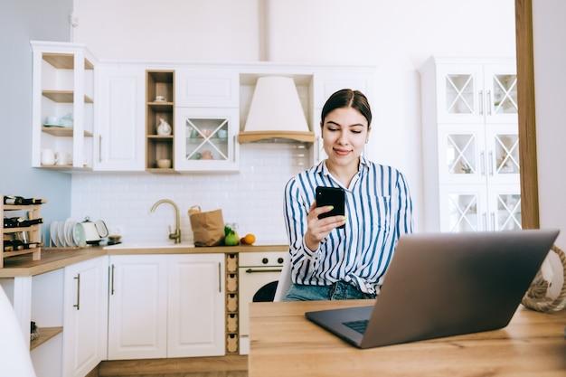 自宅のキッチンに座って、自宅で仕事をしている携帯電話とラップトップコンピューターを使用して若い白人女性。