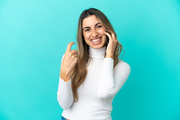 Young caucasian woman using mobile phone isolated on blue background doing coming gesture