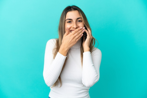 Young caucasian woman using mobile phone isolated on blue background happy and smiling covering mouth with hand