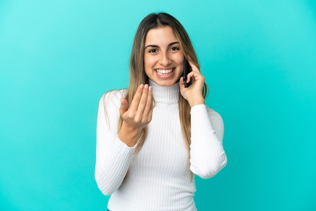 Young caucasian woman using mobile phone isolated on blue background inviting to come with hand. happy that you came