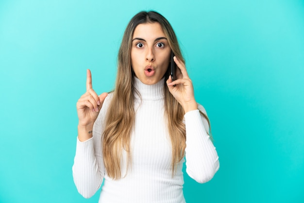 Young caucasian woman using mobile phone isolated on blue background thinking an idea pointing the finger up