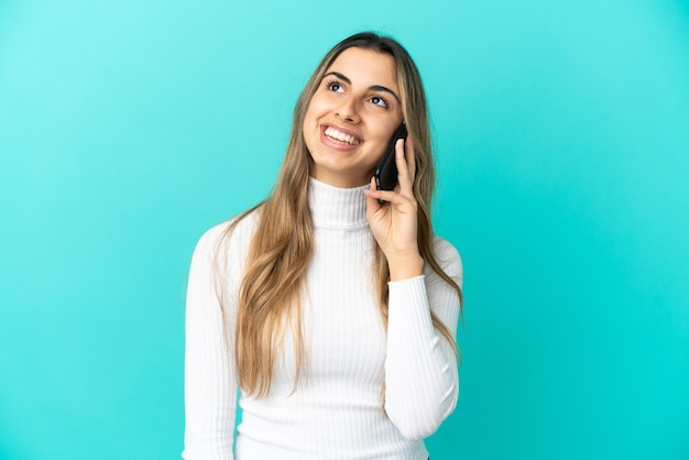 Young caucasian woman using mobile phone isolated on blue background thinking an idea while looking up