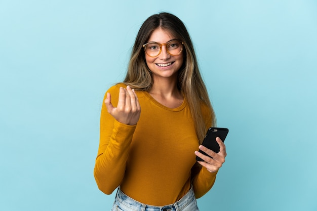 Young caucasian woman using mobile phone isolated on blue wall inviting to come with hand. happy that you came