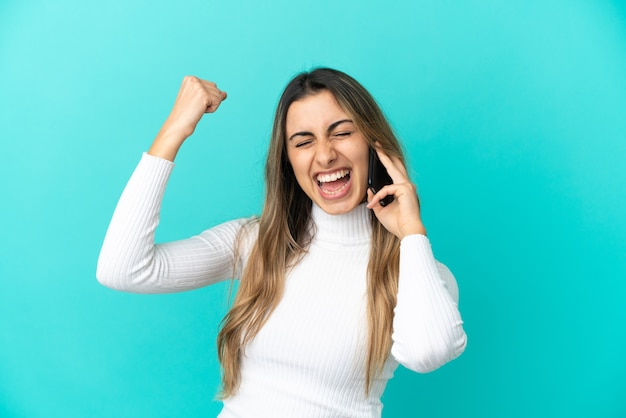 勝利を祝う青い背景で隔離の携帯電話を使用して若い白人女性