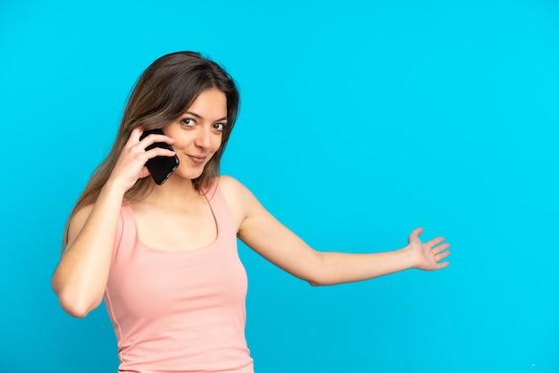 파란색 배경에 격리된 휴대전화를 사용하는 젊은 백인 여성