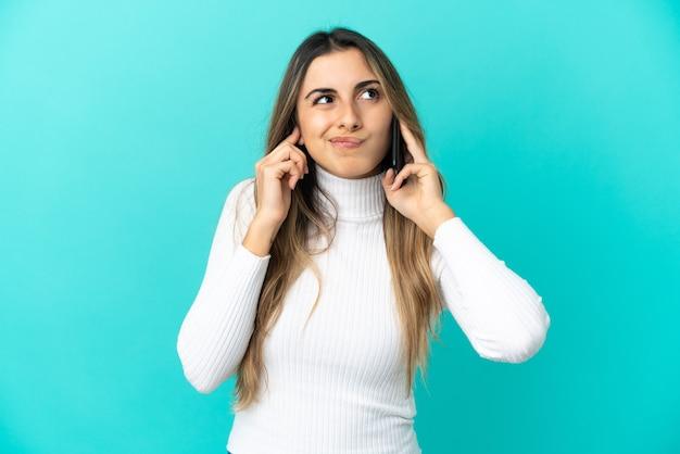青い背景で隔離の携帯電話を使用して欲求不満と耳を覆っている若い白人女性