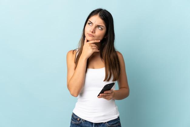 疑いを持っている青い背景で隔離の携帯電話を使用して若い白人女性