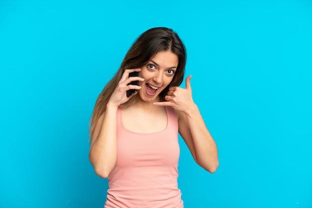 Молодая кавказская женщина с помощью мобильного телефона, изолированного на синем фоне, делая телефонный жест. перезвони мне знак