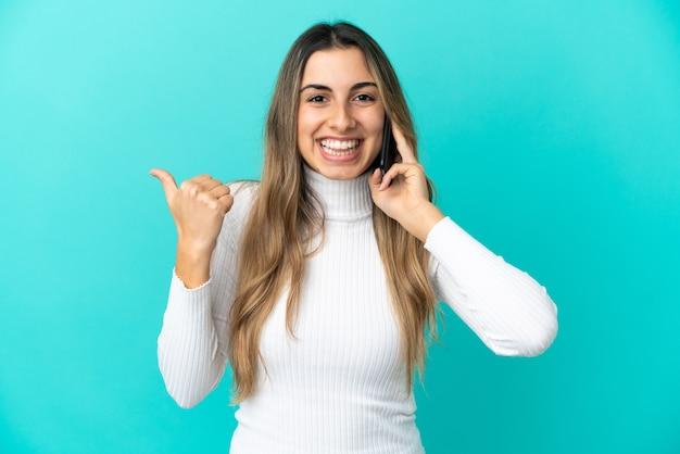 製品を提示する側を指している青い背景で隔離の携帯電話を使用して若い白人女性