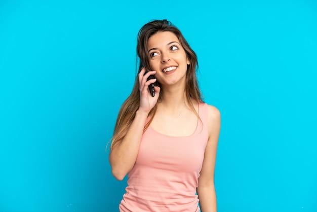 찾는 동안 아이디어를 생각하는 파란색 배경에 고립 된 휴대 전화를 사용하는 젊은 백인 여자