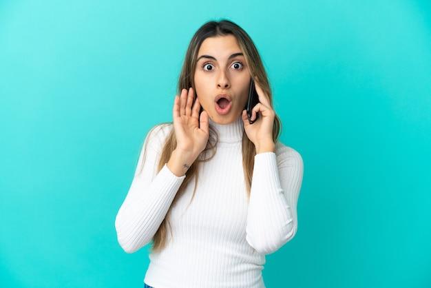 Молодая кавказская женщина разговаривает по мобильному телефону на синем фоне с удивленным и шокированным выражением лица