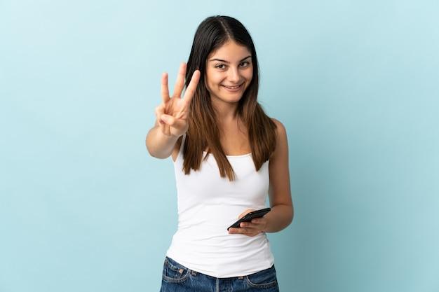 幸せな青と指で3つを数えるに分離された携帯電話を使用して若い白人女性